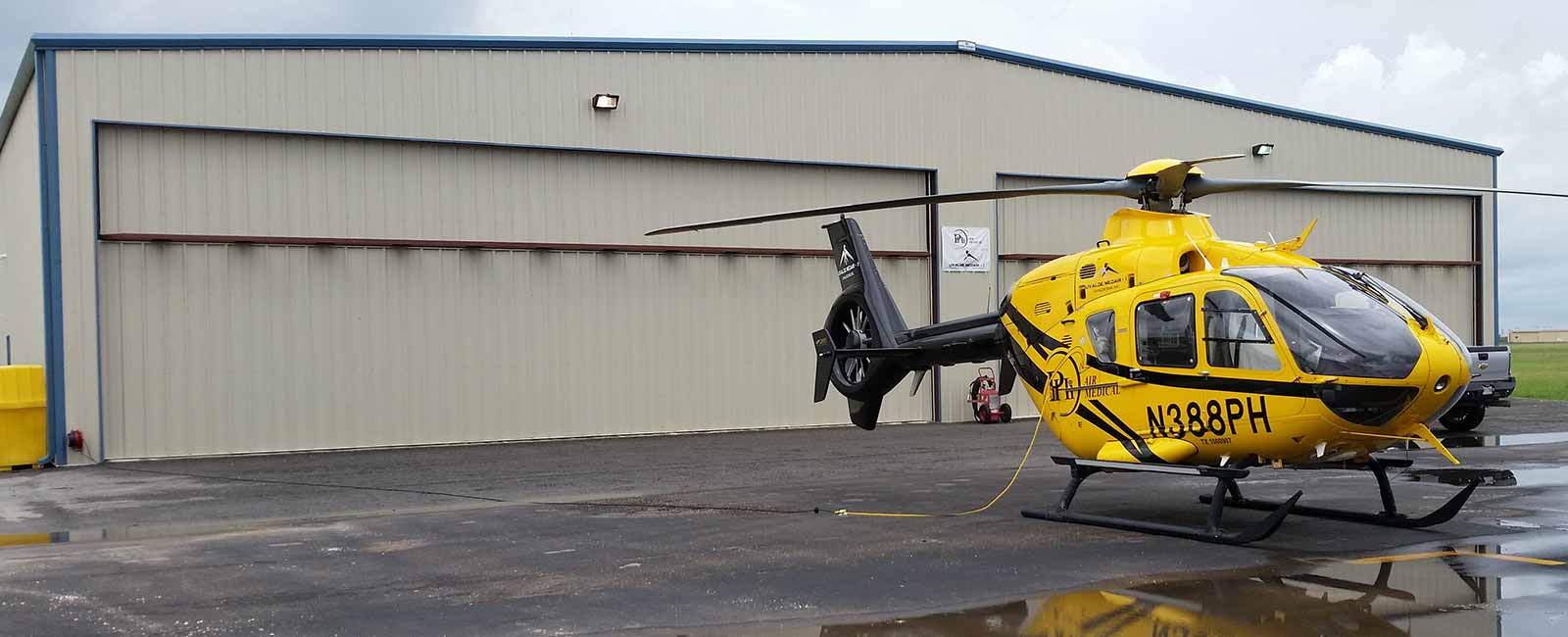 Exterior photo of a Hangar wiith a helicopter parked outside
